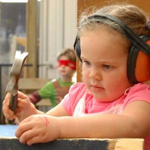 young girl using hammer in carpentry play